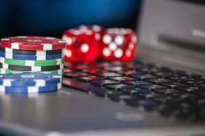 16970483-gambling-chips-and-red-dice-on-laptop-keyboard-background